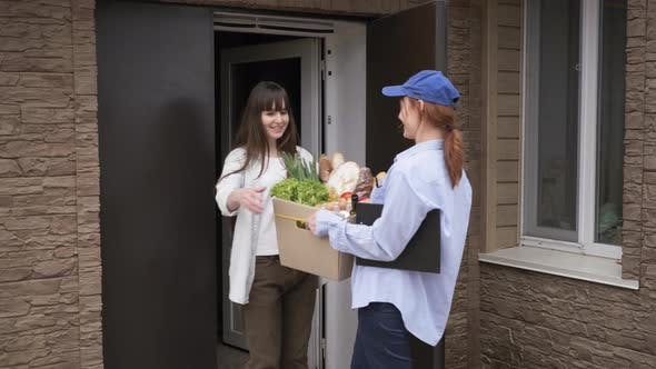 Thumbnail for Small Business, Friendly Female Courier Delivering Grocery Cart To Girl Home Ordered From Online
