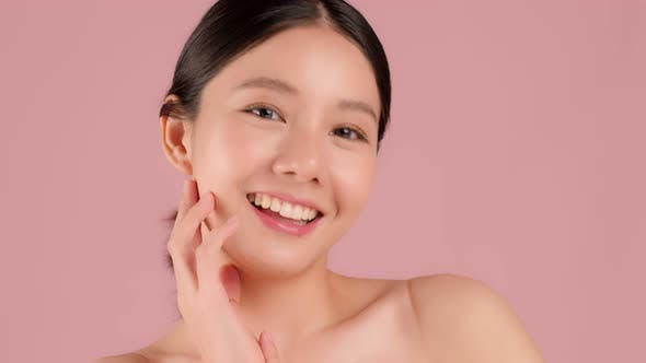 Slow motion Beauty shot of Beautiful Asian girl looking at camera isolated on pink background