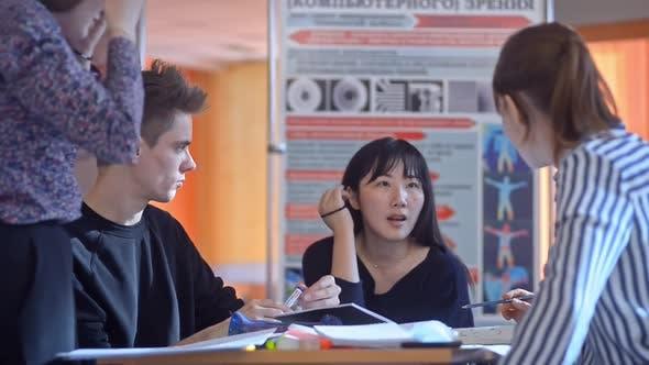 Design University Students Brainstorming Blueprint in Open Space. Irrl Coworkers Discuss Work