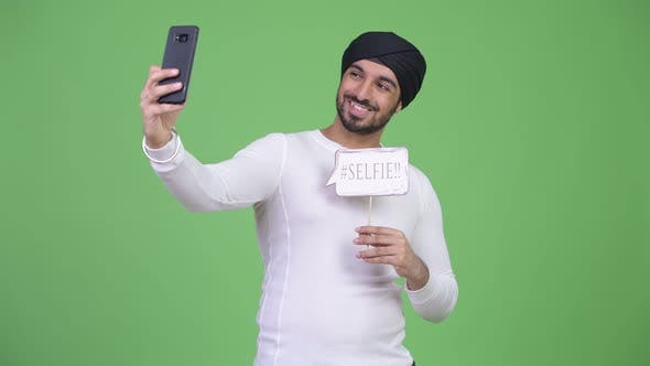 Thumbnail for Young Happy Bearded Indian Man Taking Selfie with Paper Sign