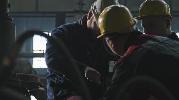 Plant Workers In Helmets Discussing Work Plan