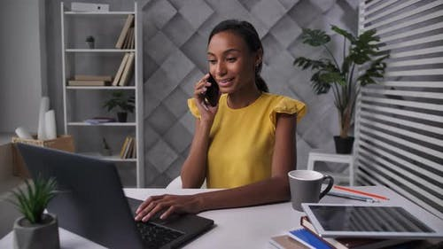 Young Woman Telecommuting at Home Office