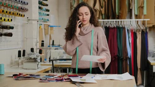 Successful tailor entrepreneur is talking on mobile phone. Woman is busy ordering fabric