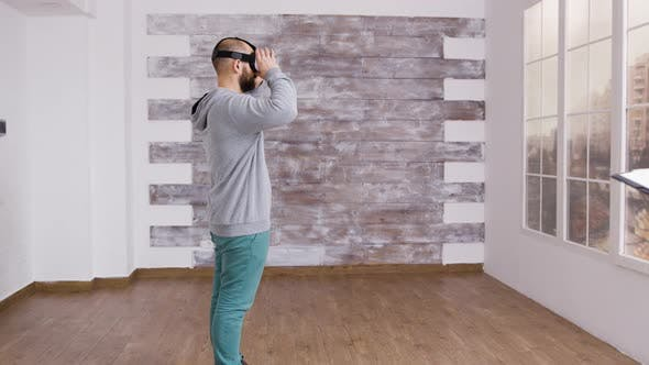 Cover Image for Caucasian Man Using Virtual Reality Headest in Empty Apartment