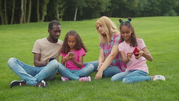 Thumbnail for Diverse Family with Girls Taking Selfie in Park