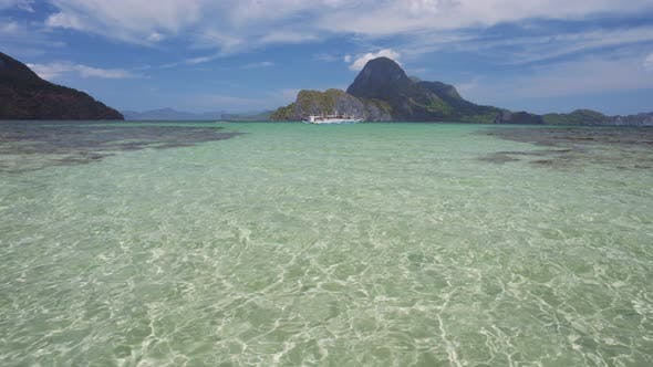 Thumbnail for Ocean Blue Lagoon with Moving Ripple Water with Banca Boats in Front of Epic Cadlao Island. Palawan