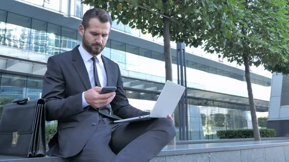 Thumbnail for Businessman Using Smartphone for Work Outside Office