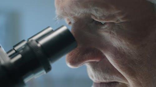 Senior Scientist schaut durch das Mikroskop
