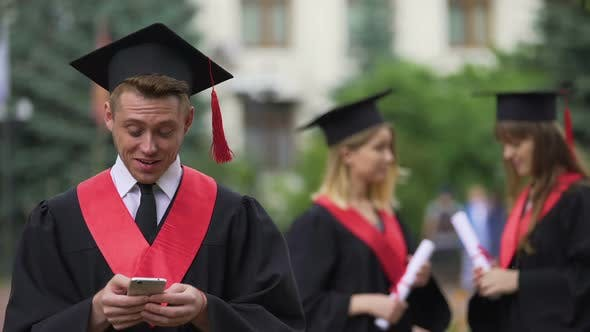 Male Graduate Reading Good News on Smartphone Before Ceremony, Astonishment