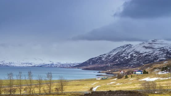 Thumbnail for Cloud rolling time lapse over snow mountain fjords in Akureyri, Iceland.