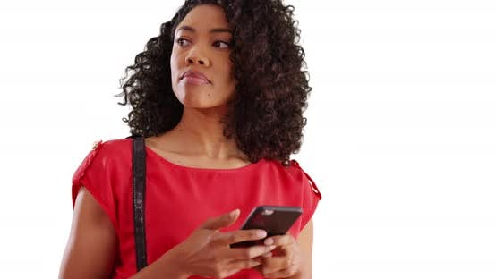Portrait of pretty African female texting on cellphone in studio with copyspace
