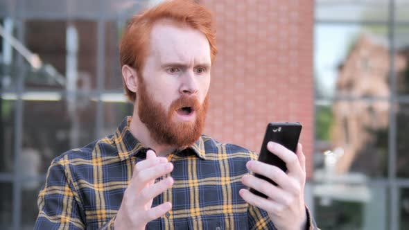 Thumbnail for Outdoor Redhead Man Upset by Loss while Using Smartphone