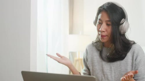 Asia businesswoman wear headphone using laptop talk to colleagues about plan in video call