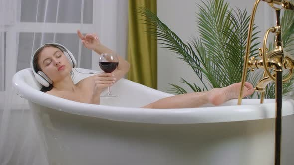Nahaufnahme der jungen Frau liegend in einer Badewanne, Musik hören mit großen Kopfhörern auf dem Kopf