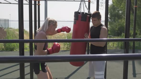 Girl Practicing Boxing With Coach Outdoors