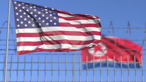 Waving Flags of the USA and North Korea Separated By Barbed Wire