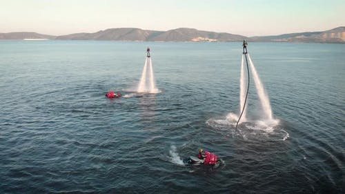 Adventurous People Hovering with Jet Packs Over Water