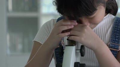 Little girl looking microscope