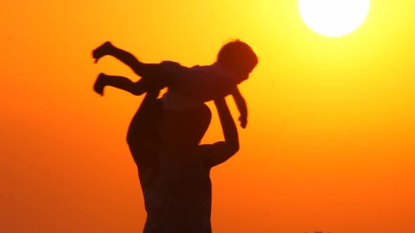 Cover Image for Mother Plays with Daughter on the Beach During Sunset. Happy Parenting Concept. Abstract Background
