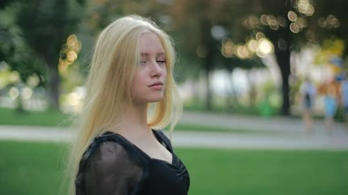 A Pensive European Girl with Long Blond Hair Walks Alone in a Park at Sunset. A Self-respecting