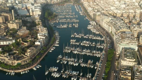 Thumbnail for Sailboats and Regular Boats Sitting in Marina Port on Malta Island, Aerial Tilt Down View