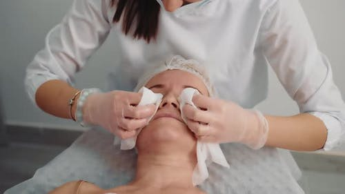 The Beautician Wipes the Face with Wet Wipes