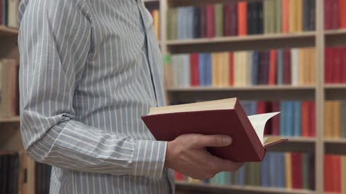 The Student Chooses a Book in the Library for Reading at your Leisure
