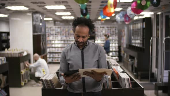 Cover Image for Black Record Shop Manager Looking at Vinyl and Smiling for Camera