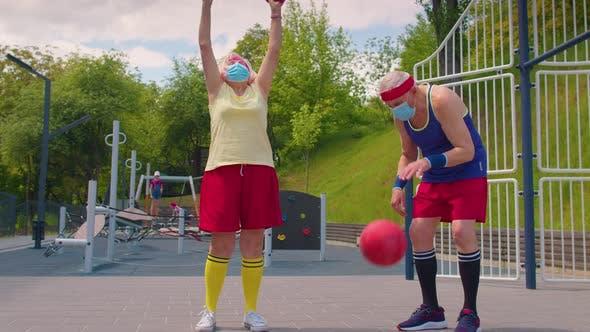 Active Senior Man Woman Playing Basketball on Sports Playground Court During Coronavirus Pandemic