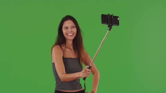 Thumbnail for Schöne junge Frau nimmt Selfies mit Smartphone auf Selfie-Stick Greenscreen