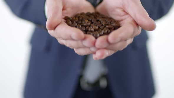 Cover Image for Coffee Beans in Cupped Hands of Man in Suit