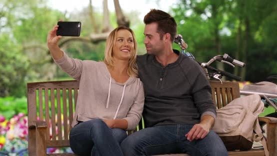 Thumbnail for Loving young couple relaxing at the park take a selfie with smartphone