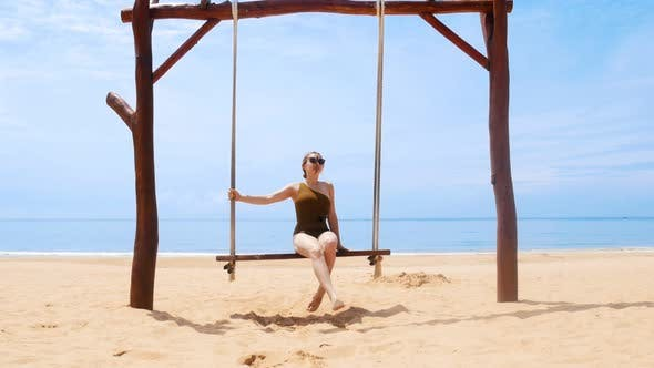 Cover Image for A Young Happy Woman Swinging on a Swings on the Beach