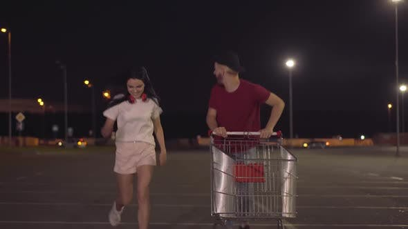Thumbnail for Two Cheerful Young People Running with Trolley Along Parking Lot at Dusk. Portrait of Happy Carefree