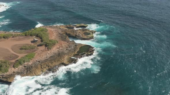 Thumbnail for Aerial drone view flying along a rocky coastline with huge ocean waves