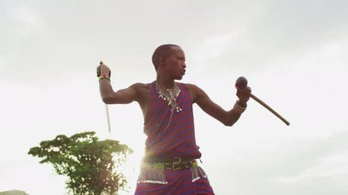 Maasai man winding up to throw a machete