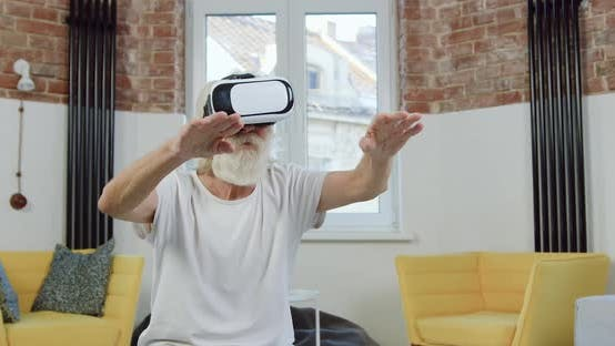 Thumbnail for 70-Aged Bearded Man in Home Clothes which Working on Virtual Screen in Augmented Reality Goggles