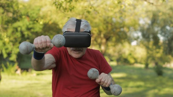 Thumbnail for Senior Old Grandfather Man in VR Headset Helmet Making Fitness Exercises with Dumbbells Outdoors