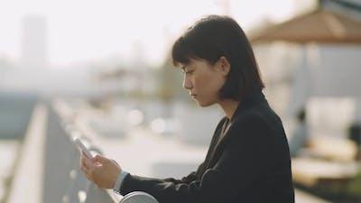 Asian Businesswoman Using Mobile Phone on Urban Embankment
