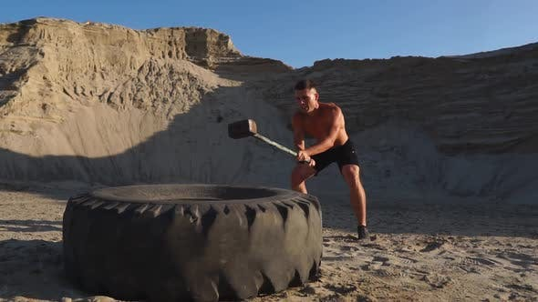 Thumbnail for Muscle Athlete Strongman Man Hits a Hammer on a Huge Wheel in the Sandy Mountains in Slow Motion