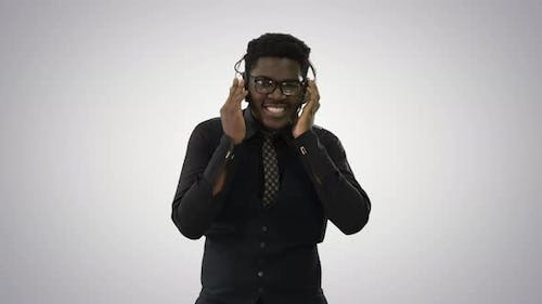 African American Man Holding Headphones with Both Hands and Grooving To Music While Looking at