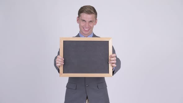 Thumbnail for Happy Young Handsome Businessman Holding Blackboard and Giving Thumbs Up