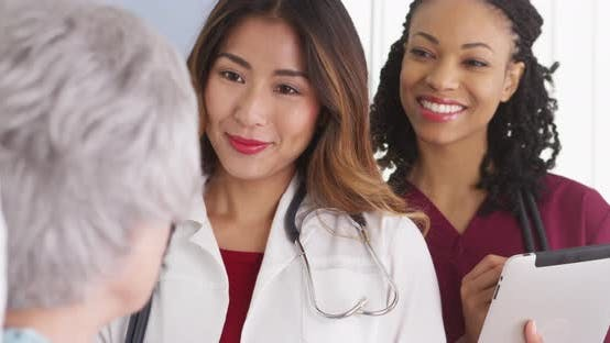 Thumbnail for Asian woman doctor and nurse talking to elderly patient in bed