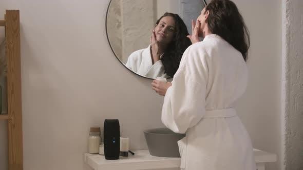 Beautiful Woman Applying Facial Cream in Bathroom
