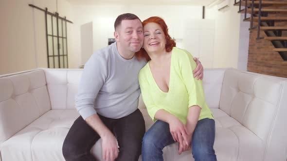 Porträt des fröhlichen kaukasischen Paares, das auf der Couch drinnen sitzt