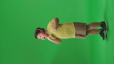 Side View Of Asian Little Boy Listening To Music With Headphones And Dancing On The Green Screen