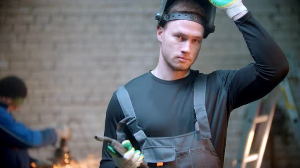Thumbnail for Young Handsome Man Walking in the Workshop Holding a Welding Instrument