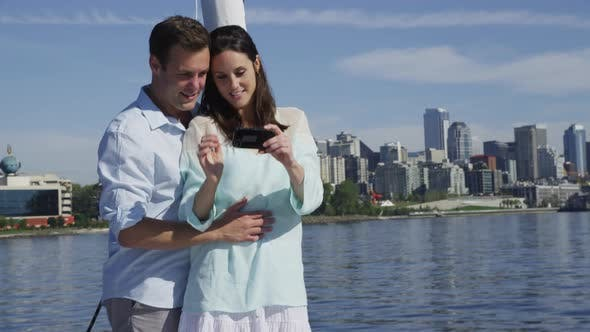 Thumbnail for Young couple on sailboat together using cell phone. Shot on RED EPIC for high quality 4K, UHD, Ultra
