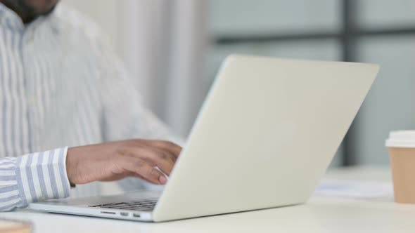 Close Up of African Man Typing on Laptop