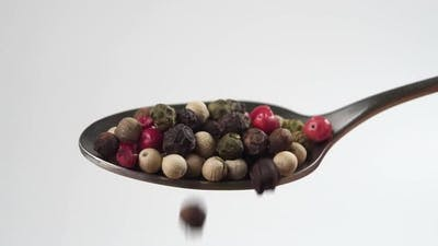 A spoonful of assorted multicolored peppercorns. Falling colored pepper seeds